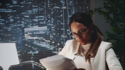African American Business Woman in Eyeglasses Reading Document