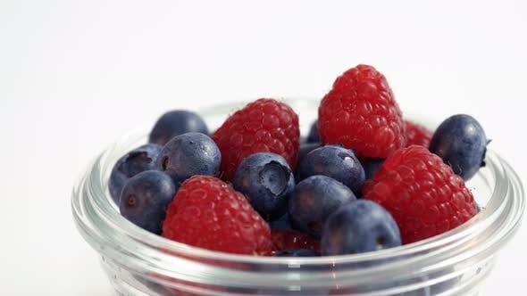 Thumbnail for Glass Bowl Of Raspberries And Blueberries Moving Across White Background Slow Motion