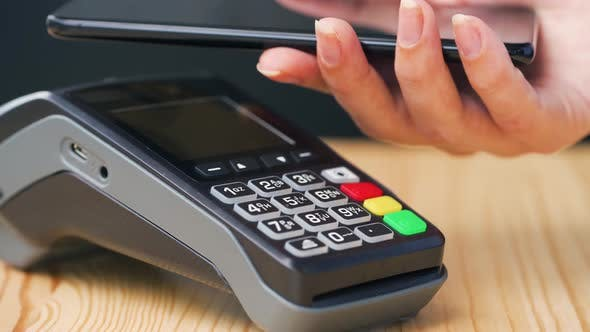 Contactless Payment with Smartphone. Wireless Payment Concept. Close-up, Woman Using Smartphone