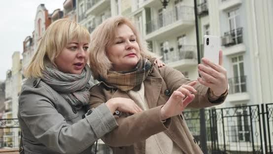 Joyful Caucasian Senior Women Posing for Selfie Photo Outdoors. Positive Carefree Retirees Spending