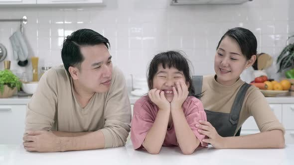Happy asian family enjoying together in kitchen at home