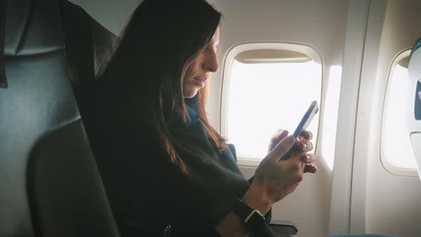 Tourist Woman Sitting Near Airplane Window and Using Mobile Phone During Flight.