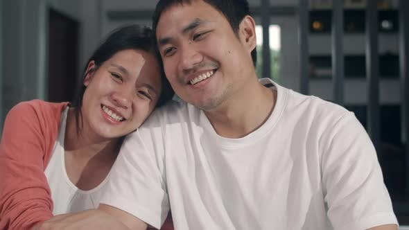 Asian Pregnant couple relax smile looking to camera at home, Mom and Dad feeling happy funny