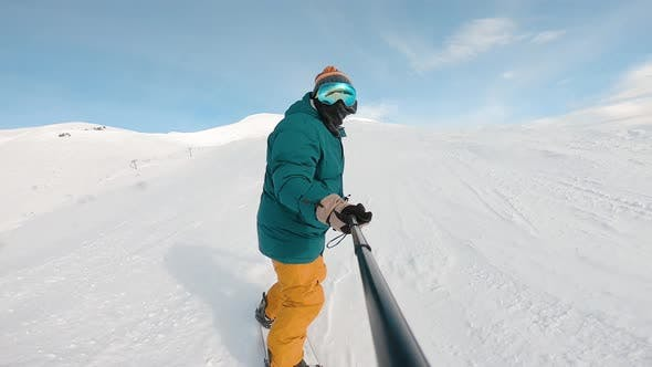 Thumbnail for Bottom View of Freeride Snowboarder Sliding Down the Snowy Slope Against the Clear Blue Sky