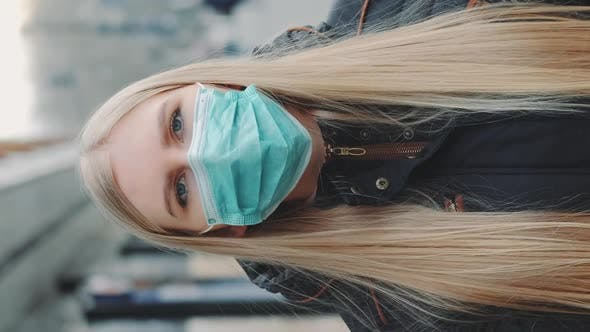 Young Blonde Woman Wearing a Protective Medical Mask on the Street