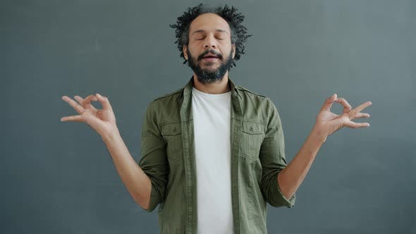 Slow Motion Portrait of Enlightened Mixed Race Man Meditating Holding Hands in Namaste Gesture