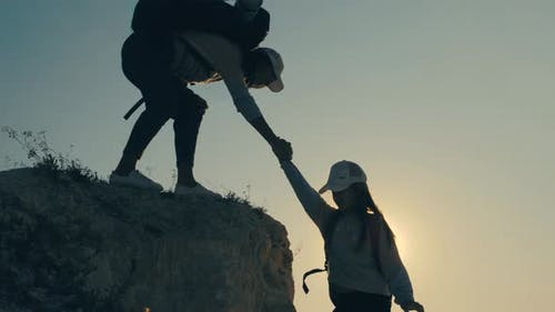 Girl Helps Her Friend Climb Up the Last Section of Mountain