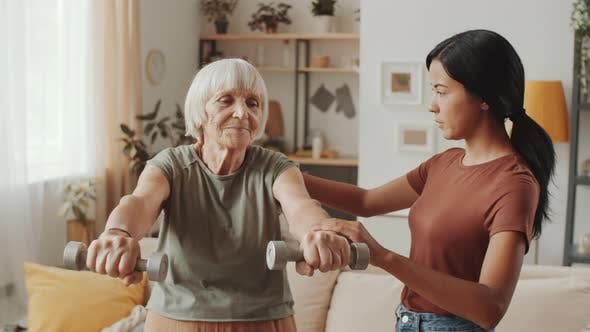 Thumbnail for Old Woman Exercising with Dumbbells with Help of Caregiver