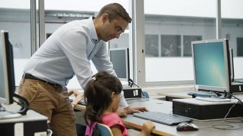 Girl Typing on Keyboard for First Time with Help of Teacher
