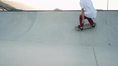 Skillful Skateboarder Training in Bowl Ramp Among the Mountains