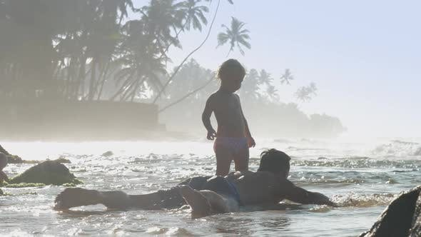 Thumbnail for Father and Daughter Play on Shore Against Shining Ocean