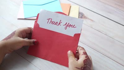 Child Hand Holding Thank you Letter on Table