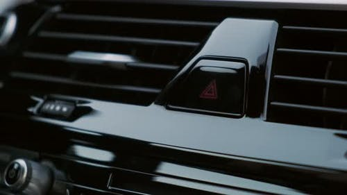 A man presses the emergency button in the car. Close up. Button blinks lights flash