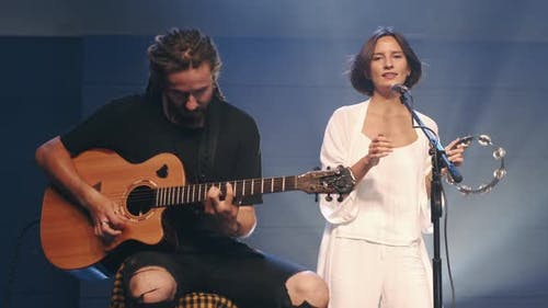 Female Singer with Tambourine and Musician Playing Guitar Performing on Stage