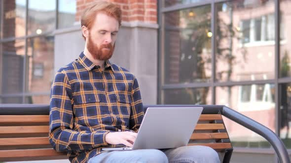 Thumbnail for Redhead Beard Young Man working on Laptop, Sitting Outdoor on Bench