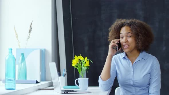 Cover Image for Young Black Businesswoman Gossiping on Phone