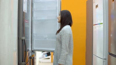 Young Woman in a Home Appliance Shop Chooses a Refrigerator