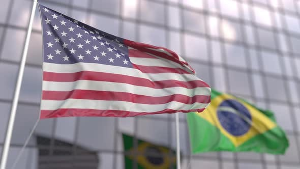 Flags of the United States and Brazil in Front of a Skyscraper