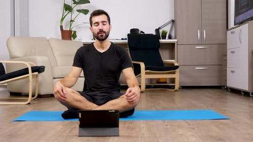 Man Meditating in Lotus Yoga Pose and Looking at a Digital PC