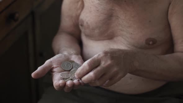 Poor Elderly Man Counting Coins in a Hand