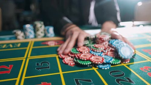 Casino, Gambling, Poker, People and Entertainment Concept - Close Up of Poker Player with Chips at