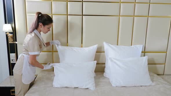 Hotel Cleaning Concept. Portrait of Young Pretty Maid in Uniform Making Bed in Bright Room Touching