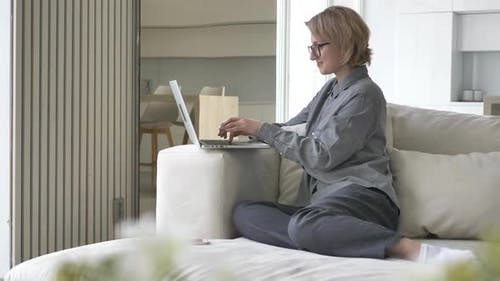 Concentrated Short Haired Blonde Young Woman Types on Laptop