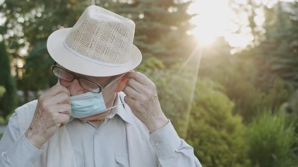 Senior Man with Glasses Wears Medical Mask and Looking Into Camera Outdoors