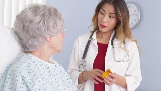 Thumbnail for Asian doctor talking to elderly woman in bed about prescription medication