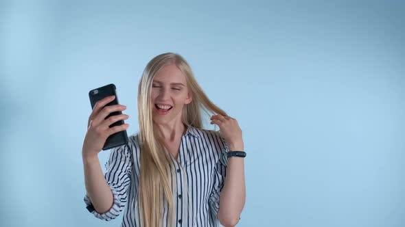 Attractive Blonde Lady Making Selfie on Smartphone on Blue Background