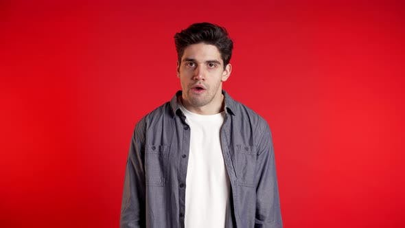 Thumbnail for Frustrated Bored European Man in Denim Wear Over Red Wall Background.