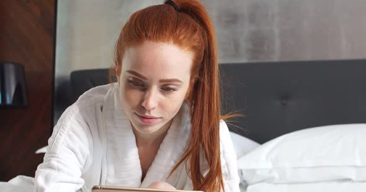 Young Redhead Woman Watching Movie on Tablet Computer Lying on Bed in Hotel Room