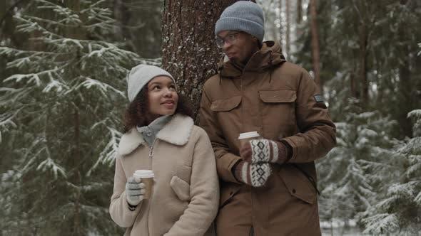 Thumbnail for Paar spaziert im Wald und trinkt Kaffee