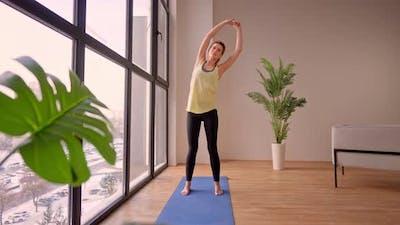 Woman in Sportswear Stretching Near Window