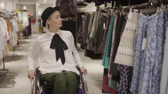 Thumbnail for Woman in Wheelchair Shopping for Skirt in Clothing Store