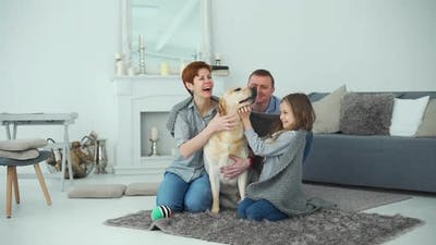 Family Enjoying Home Life with Their Labrador Dog