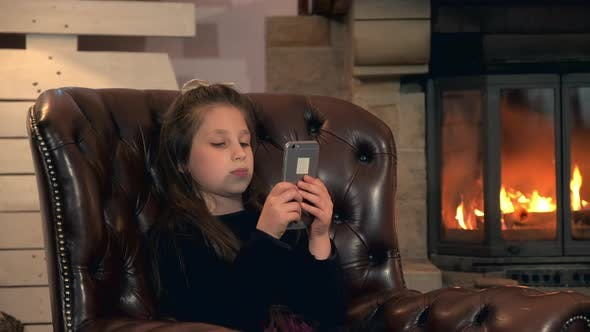 Thumbnail for Small Girl Playing Games on Smartphone Near the Fireplace