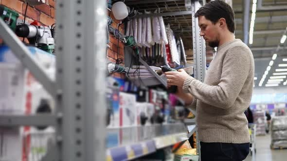 Young Man Choosing a Drill in the Hardware Store in Big Supermarket