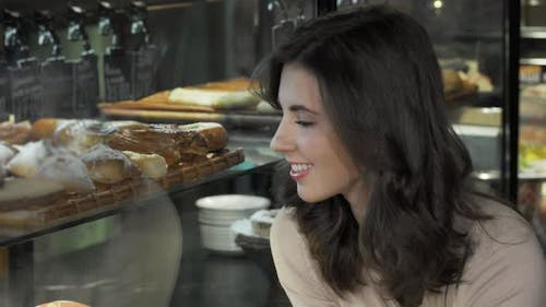 Happy Beautiful Woman Choosing Dessert To Buy From the Bakery Display