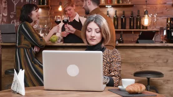 Thumbnail for Woman Typing on Her Laptop While People Are Chatting at the Bar