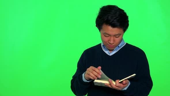 Thumbnail for A Young Asian Man Reads a Book While Standing, Eventually Looks Up - Green Screen Studio