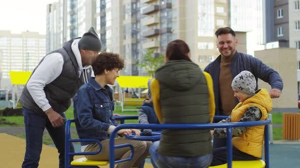 Thumbnail for Two Happy Families Enjoying Roundabout Ride in Playground