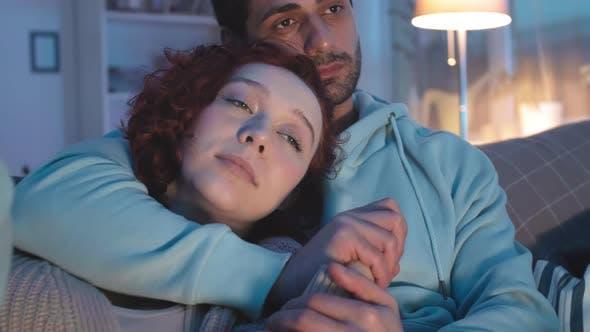 Multiethnic Couple Snuggling at Night Indoors