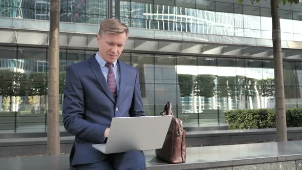 Thumbnail for Pensive Businessman Sitting Outside and working on Laptop