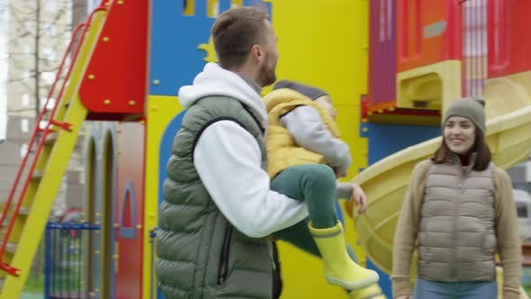 Cover Image for Loving Caucasian Dad and Son Spinning Around Together at Playground