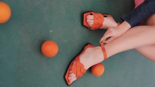 Orange Female Sandals on the Legs Vertical Video