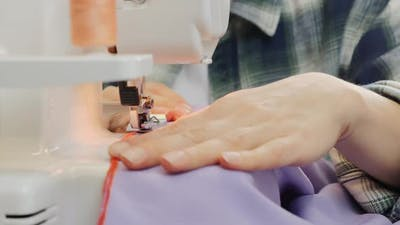 Close up of woman fingers sew on sewing machine. Sewing concept