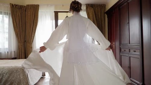 Woman in Beautiful Developing White Robe Walks Through Bedroom To Balcony.