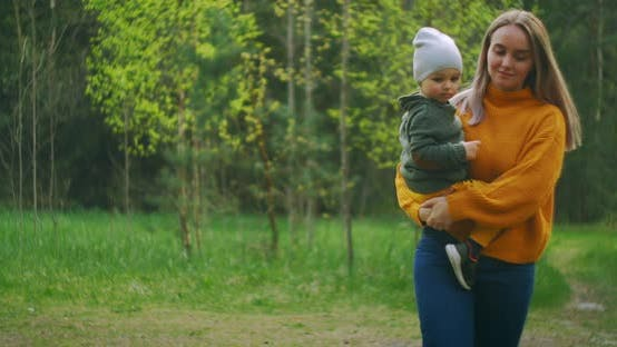 Thumbnail for In Slow Motion, a Mother and Son Walk Through the Park in Sweaters