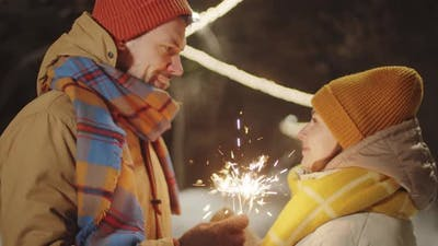 Romantic Couple Standing with Christmas Sparklers Outdoors